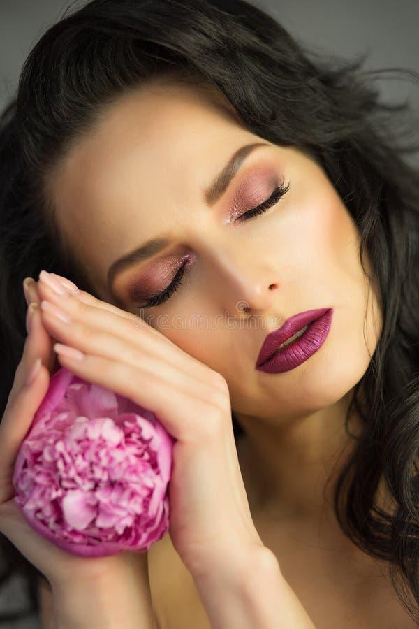 Schoonheidsportret van verleidelijke donkerbruine dame met roze pioen flowe royalty-vrije stock foto's