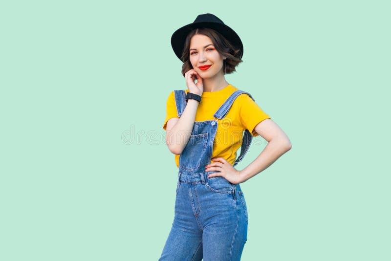 Schoonheidsportret van vrij jong hipstermeisje in blauwe denimoverall, geel overhemd die, zwarte hoed zich met hand op taille bev stock fotografie