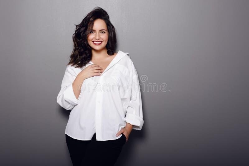 Schoonheidsportret van vrolijke donkerbruine vrouw, slijtage in wit overhemd en zwarte broek, die op een grijze achtergrond wordt royalty-vrije stock afbeelding