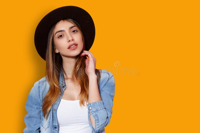 Schoonheidsportret van vrolijke jonge vrouw in hoed het stellen met houding die camera bekijken die, op een gele achtergrond word stock fotografie