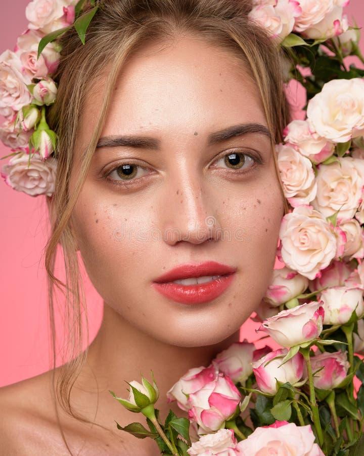 Schoonheidsportret van vrouwengezicht met sproeten en een kroon van roze bloemen in haar stock fotografie