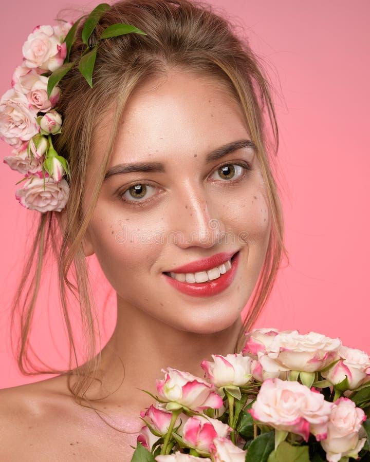 Schoonheidsportret van vrouwengezicht met sproeten en een kroon van roze bloemen in haar stock foto