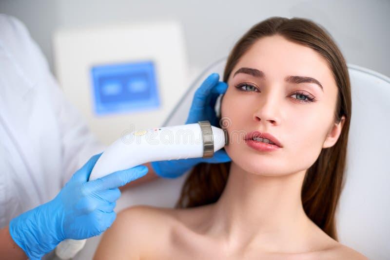 Schoonheidsspecialist arts die rf-opheffende procedure voor onberispelijk vrouwengezicht doen die in een schoonheidssalon leggen  stock afbeelding