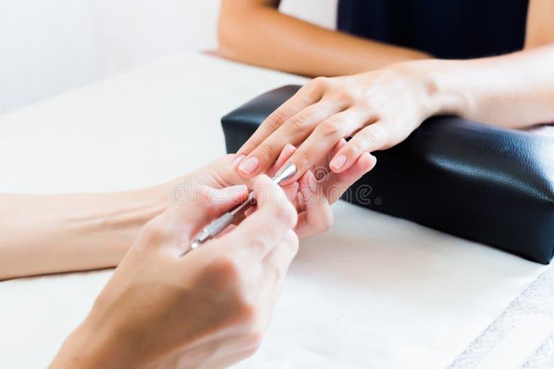 Schoonheidsspecialist die een manicure in salon doen stock afbeelding