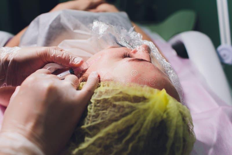 Schoonheidsspecialist die injectie in vrouwen` s gezicht maken, close-up Biorevitalizationprocedure stock foto
