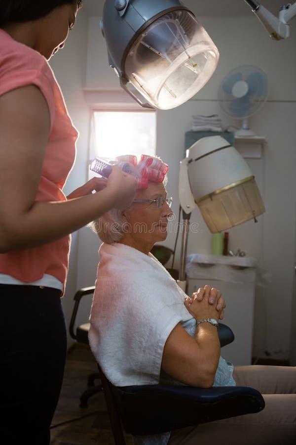Schoonheidsspecialist die krulspelden verwijderen uit hoger vrouwenhaar stock afbeelding