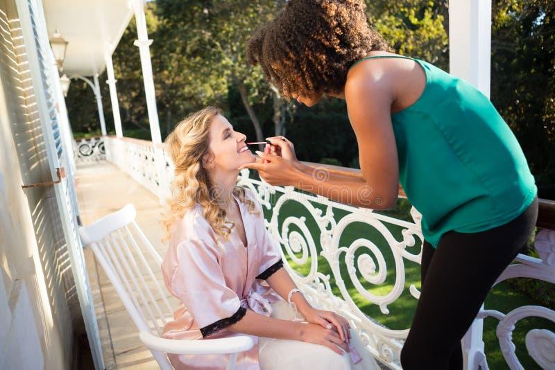 Schoonheidsspecialist die lipgloss toepassen op bruid in balkon stock foto's