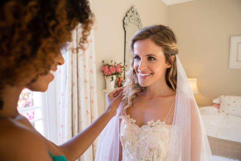 Schoonheidsspecialist die omhoog bruid thuis kleden royalty-vrije stock foto