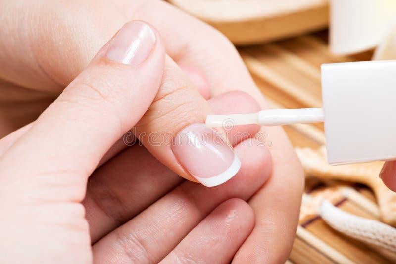 Schoonheidsspecialist die spijkervernis op een duimnagel toepassen. stock afbeelding