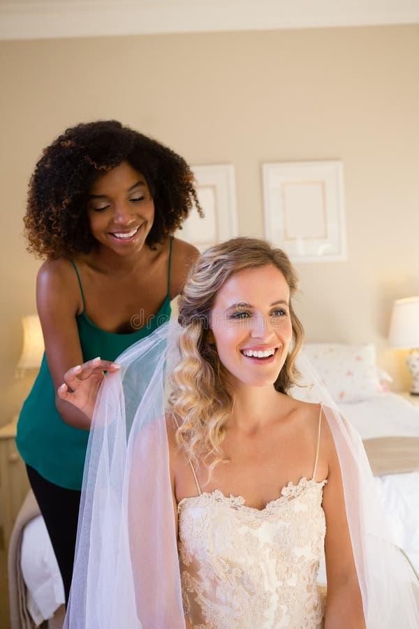 Schoonheidsspecialist het aanpassen sluier van bruidhaar terwijl thuis het zitten op bed royalty-vrije stock fotografie