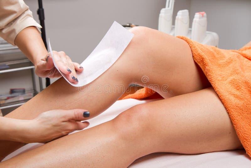 Schoonheidsspecialist het in de was zettende been van een vrouw stock afbeelding