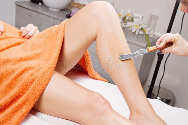 Schoonheidsspecialist Waxing het Been van een Vrouw stock afbeeldingen