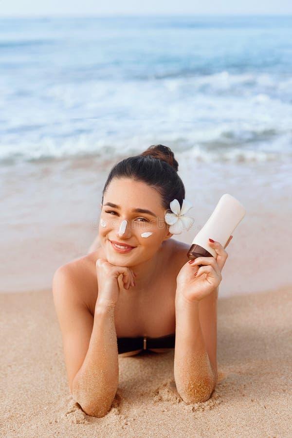 Schoonheidsvrouw in de Flessen van de Bikiniholding van Zonnescherm in Haar Handen Skincare Een Mooi Wijfje die Zonroom toepassen stock afbeelding