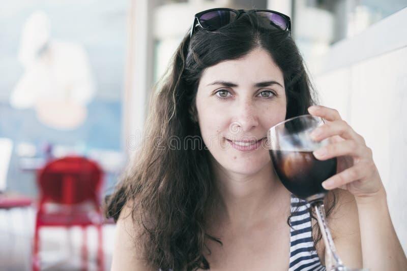 Schoonheidsvrouw die een kop van cokes drinken stock afbeeldingen