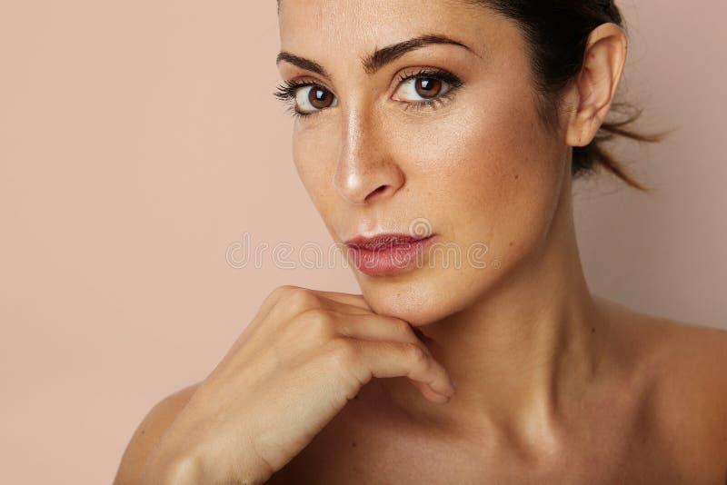 Schoonheidsvrouw die met grote bruine ogen en donkere wenkbrauwen camera over lege beige achtergrond bekijken Model met lichte na royalty-vrije stock afbeeldingen