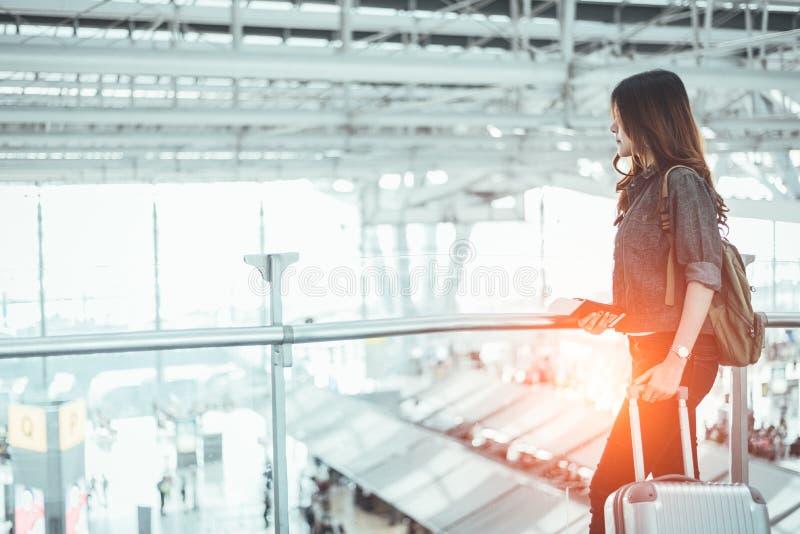 Schoonheidsvrouw die op startvlucht wachten in luchthaven Aziatische vrouw met karretjekoffer Mensen en levensstijlenconcept royalty-vrije stock foto's