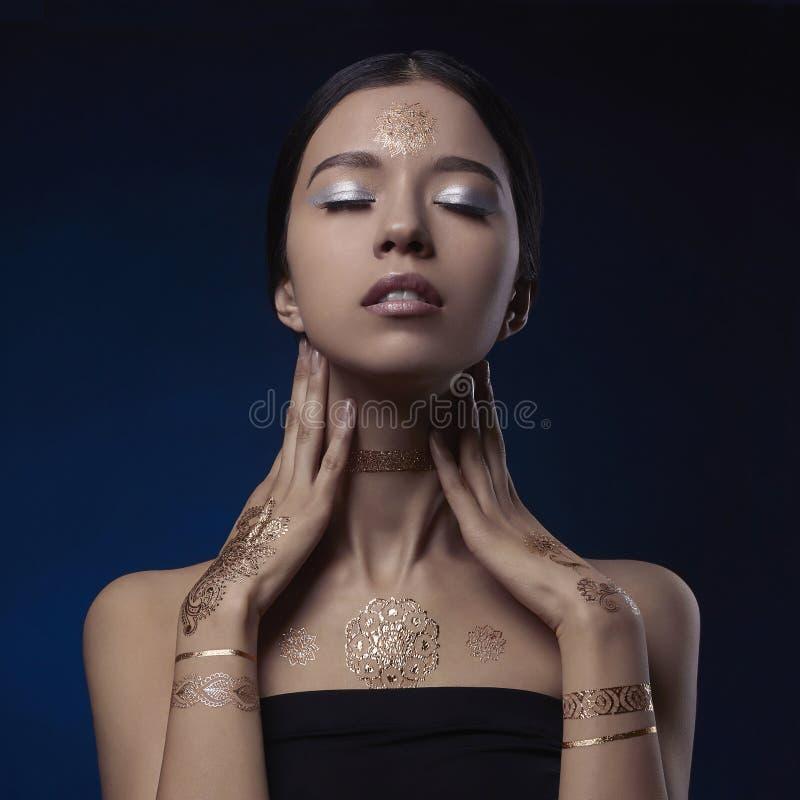 Schoonheidsvrouw met gouden Mehendi-patroon stock foto's