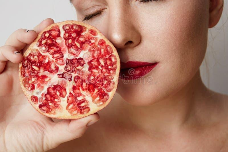 Schoonheidsvrouw met oranje granaatappel die in de helft over witte achtergrond wordt gesneden Aantrekkelijk vers vitamineconcept royalty-vrije stock fotografie