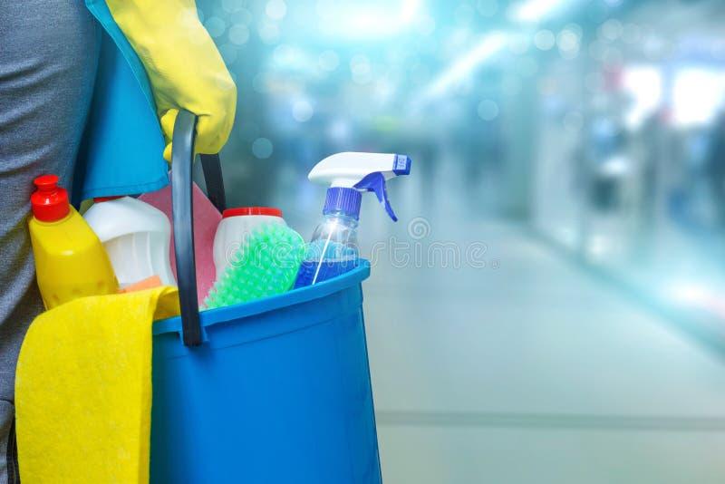 Schoonmaakster met een emmer en schoonmakende producten stock foto