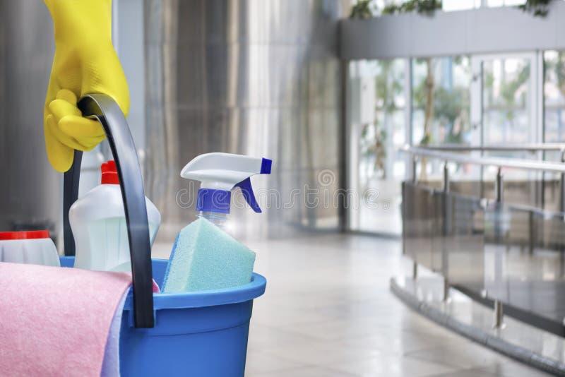 Schoonmaakster met een emmer en schoonmakende producten stock fotografie
