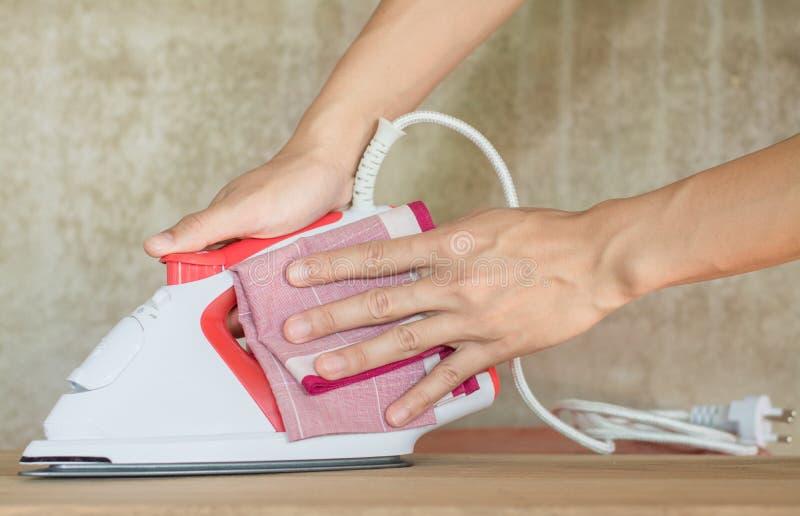 Schoonmakend ijzer, sluit omhoog hand van vrouwen schoonmakend ijzer door kleren royalty-vrije stock fotografie