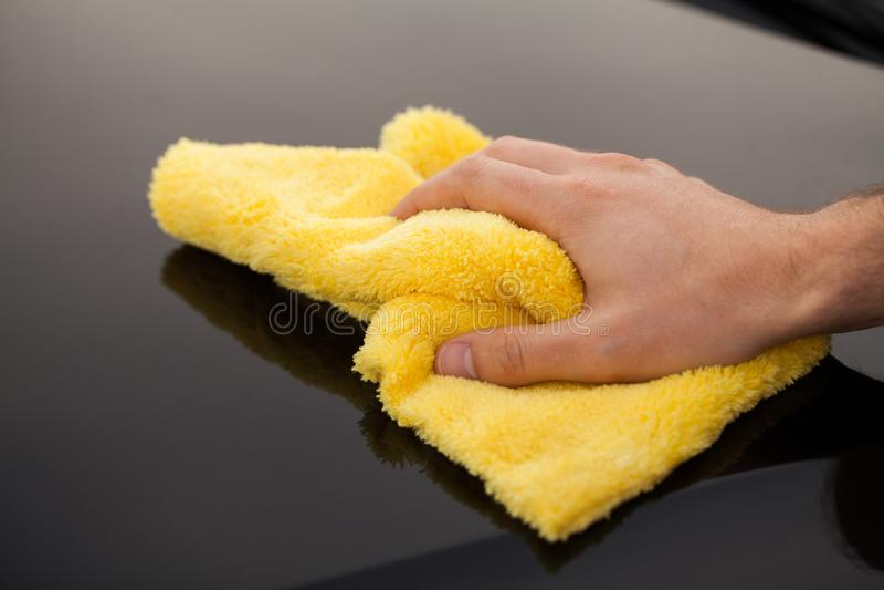 Schoonmakende auto De mens houdt microfiber in hand en poetst de auto op stock afbeelding