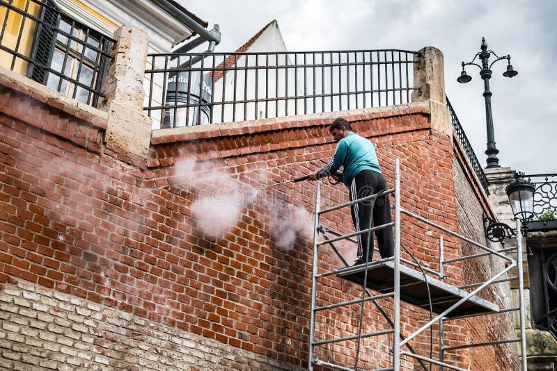 Schoonmakende de dienstarbeider die oude de bouwvoorgevel wassen royalty-vrije stock fotografie