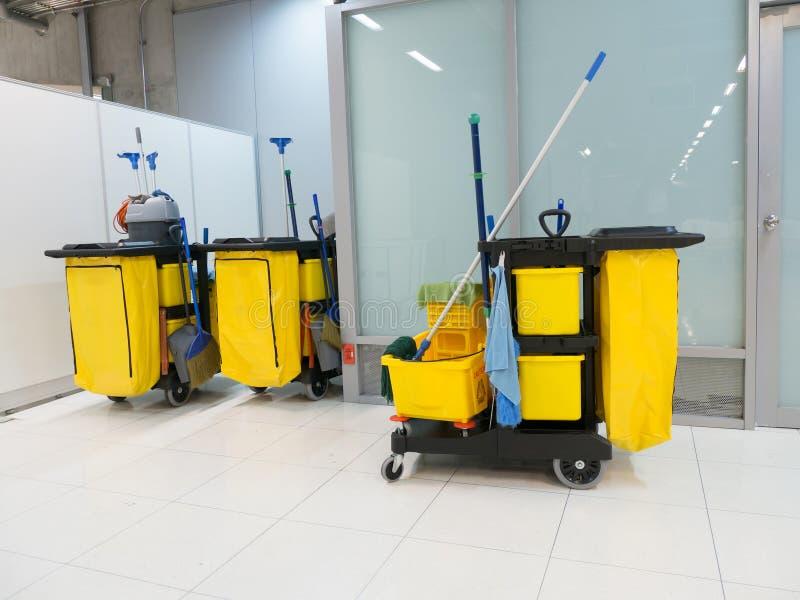 Schoonmakende Kar in de post De schoonmakende hulpmiddelenkar en de Gele zwabberemmer wachten op het schoonmaken Emmer en reeks v stock foto's