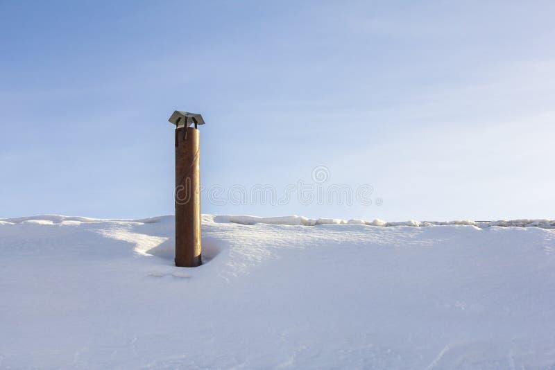 Schoorsteen op het snow-covered dak van het huis tegen de blauwe hemel royalty-vrije stock foto