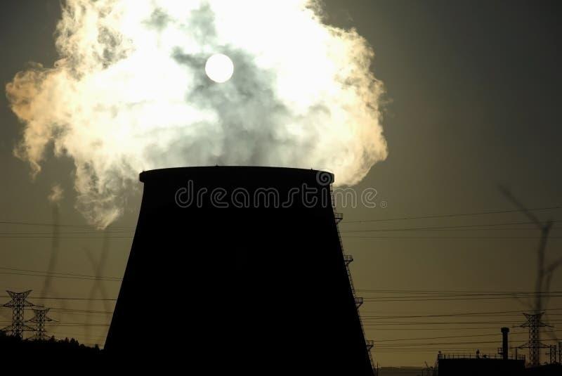 Schoorsteen van elektrische centrale tegen zon stock afbeeldingen