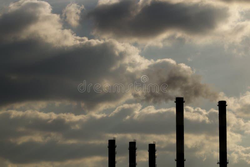 Schoorstenen met stoomproductie van een thermische krachtcentrale De bewolkte hemel wordt verontreinigd door rook van de schoorst royalty-vrije stock afbeelding