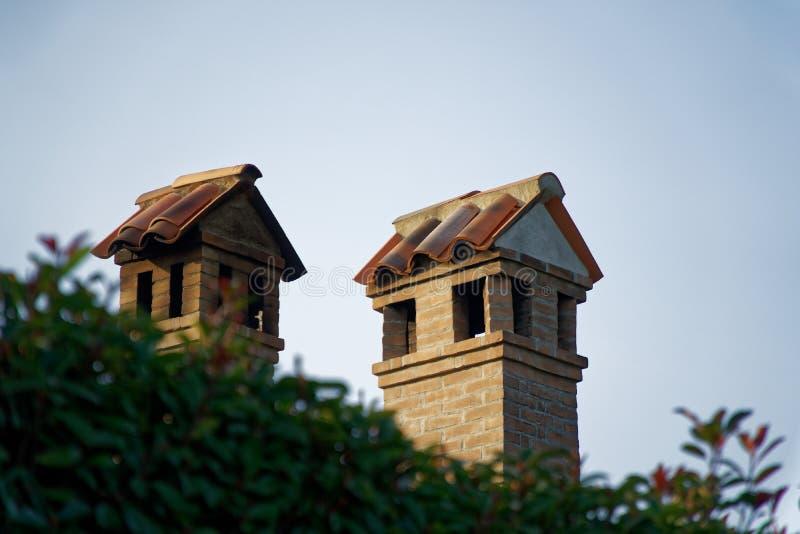 Schoorstenen van Baksteen en roestvrij staal op een betegeld Dak worden gebouwd, de Stijl die van Italië stock fotografie