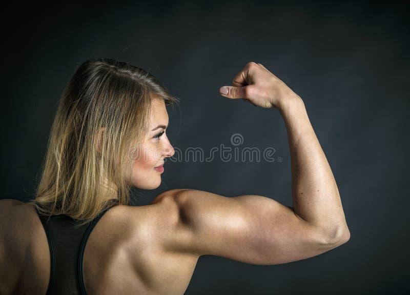 Schoot de sport jonge vrouw met perfect lichaam die bicepsen, fitness meisjesstudio tonen over op grijze achtergrond stock fotografie