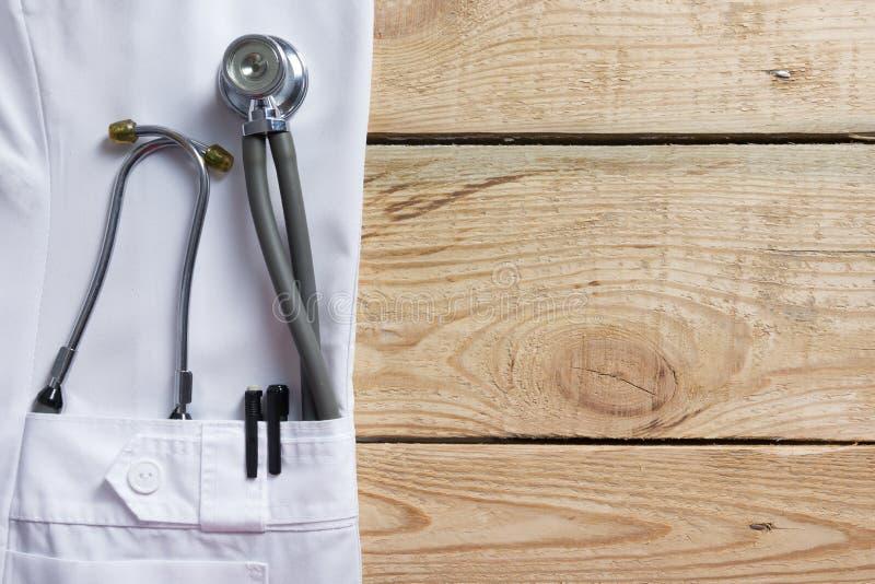 Schoot de witte de laagzak van het artsenlaboratorium met pen, stethoscoop, close-up op uitstekende houten achtergrond De ruimte  royalty-vrije stock afbeelding