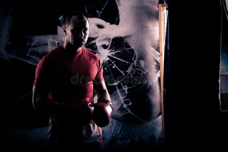 Schopbokser het in dozen doen als oefening voor de grote strijd Het ponsenzak van bokserklappen Jonge boksertreinen op ponsenzak stock afbeelding