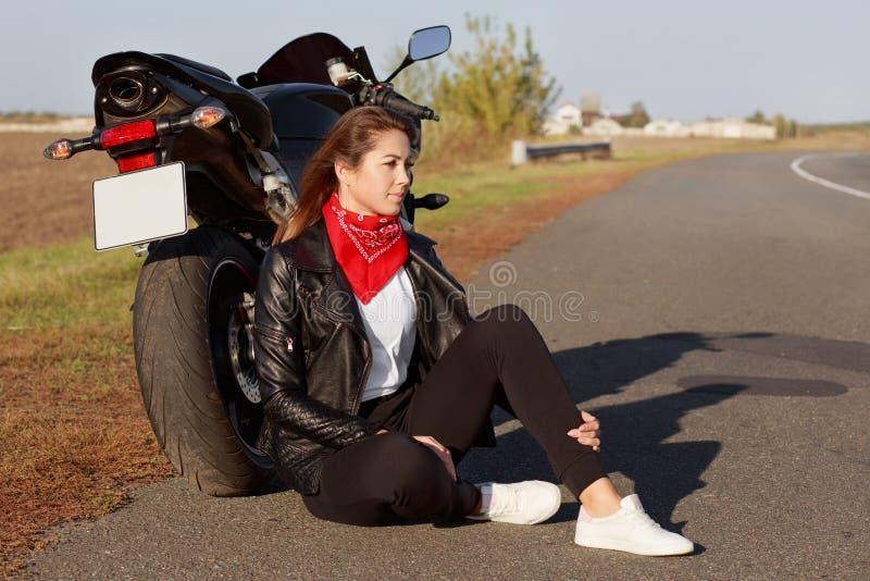 Schoss seitlich vom nachdenklichen jungen erfahrenen weiblichen Radfahrer trägt Lederjacke, weiße Turnschuhe, sitzt nahe Motorrad lizenzfreie stockbilder