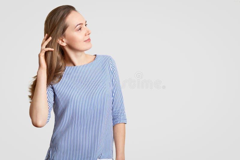 Schoss seitlich von der durchdachten stilvollen Frau hält Hand auf Haar, hat durchdachten Ausdruck, trägt gestreifte Kleidung, Mo lizenzfreie stockbilder