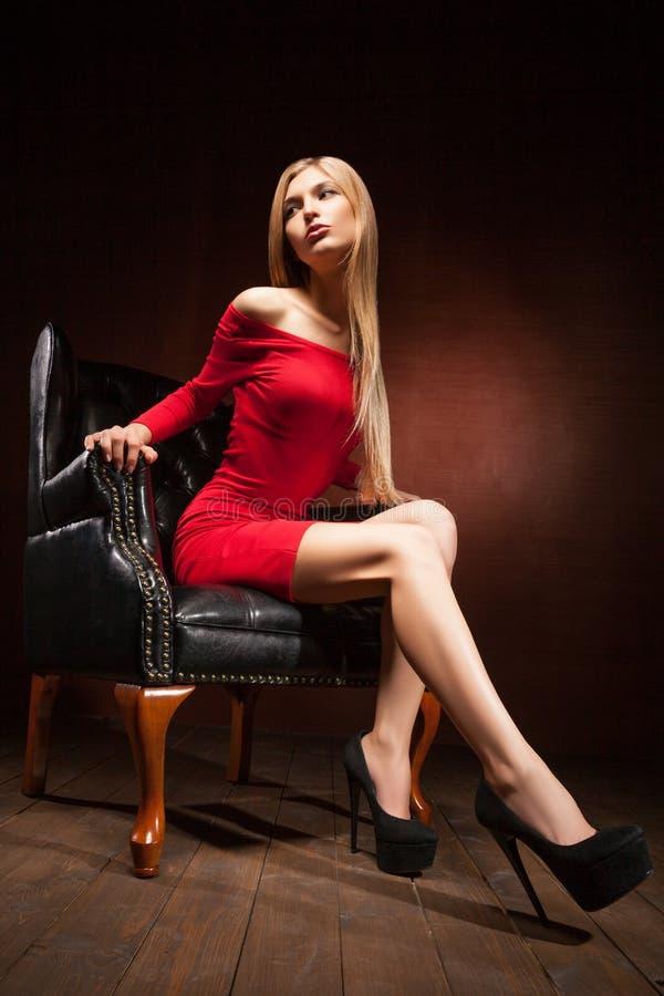 Schot die van mooie vrouw rode kledingszitting dragen stock fotografie