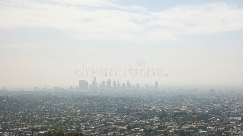 Schot van de horizon van de binnenstad van Los Angeles gebaad in smog van Griffith Park stock afbeelding