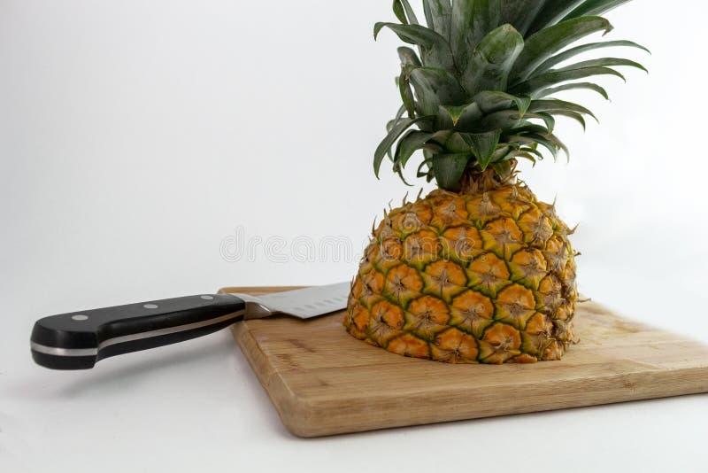 Schot van drie - de kwarten van een ananas snijden op een hakbord met een mes stock afbeeldingen