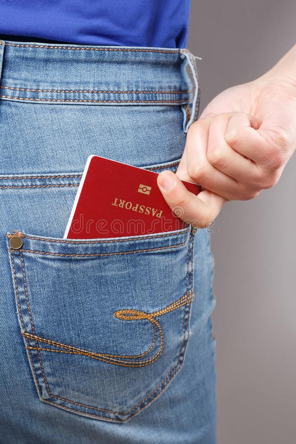 Schot van jonge vrouw erachter in uitgeput jeans en paspoort in een zak stock afbeelding