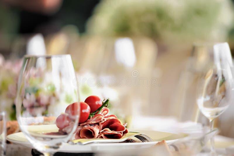 Schot van kersentomaten en ham op een plaat in een restaurant worden opgemaakt dat royalty-vrije stock foto