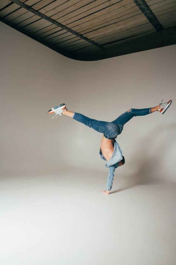 Schot van sprongvoeten omhoog, van gekke, gekke, vrolijke, succesvolle, gelukkige kerel in toevallige uitrusting, jeans, die met  stock foto
