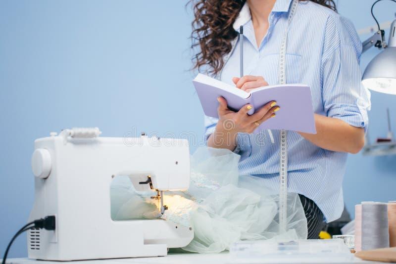 Schot van vrouw die nota's naast naaimachine maken stock foto