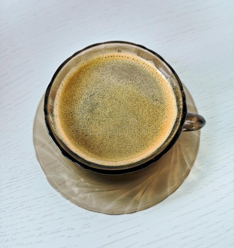 Schotel en kop van aangemaakt bruin glas met zwarte koffietribune op een witte houten lijst royalty-vrije stock afbeeldingen