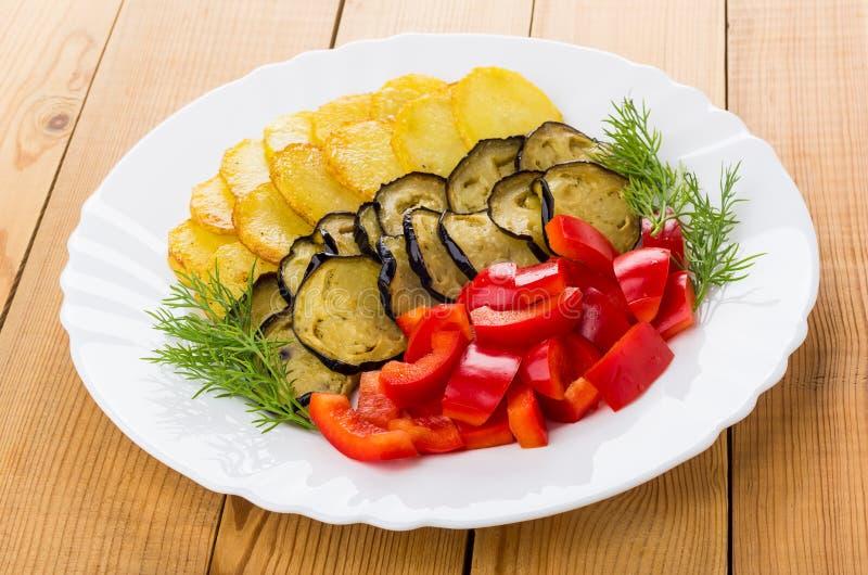Schotel met gebraden aardappel, aubergine, paprika, dille op lijst royalty-vrije stock afbeelding