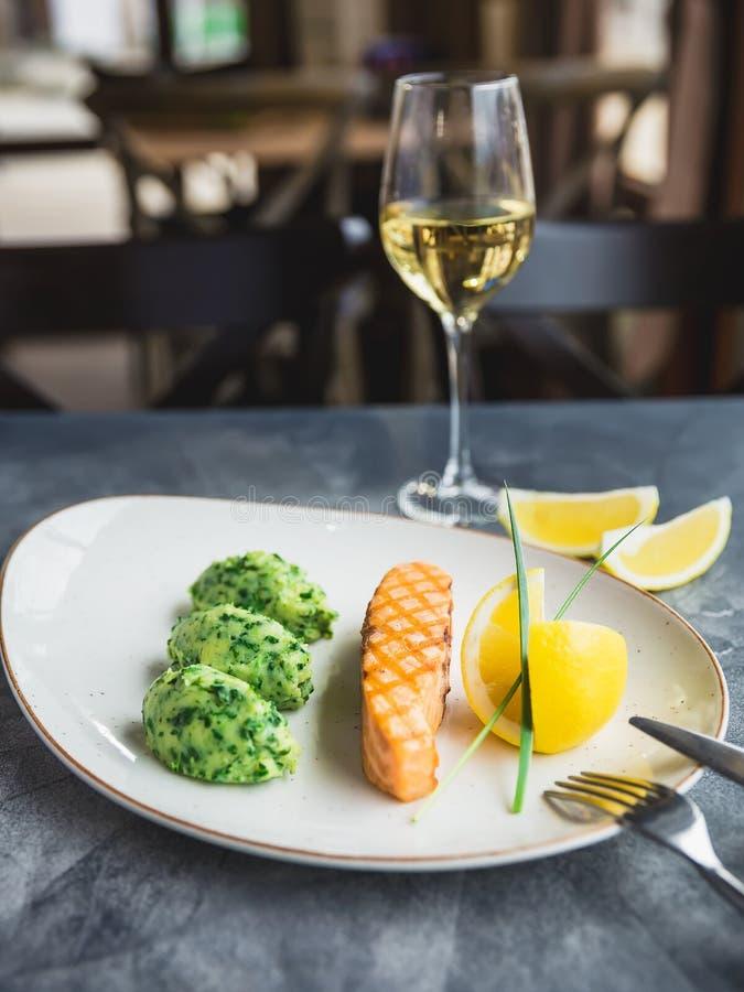 Schotel met geroosterde zalm met citroenplakken en glas witte wijn op lijst Sluit omhoog mening stock afbeeldingen