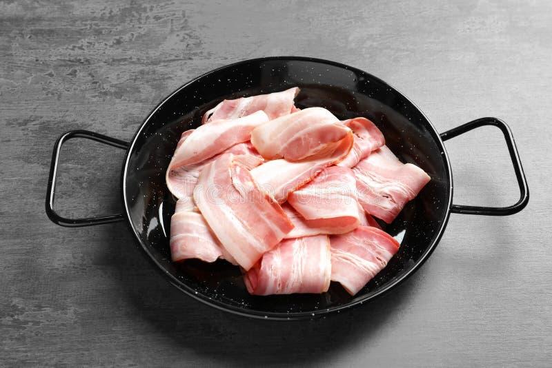 Schotel met plakjes van bacon stock afbeelding