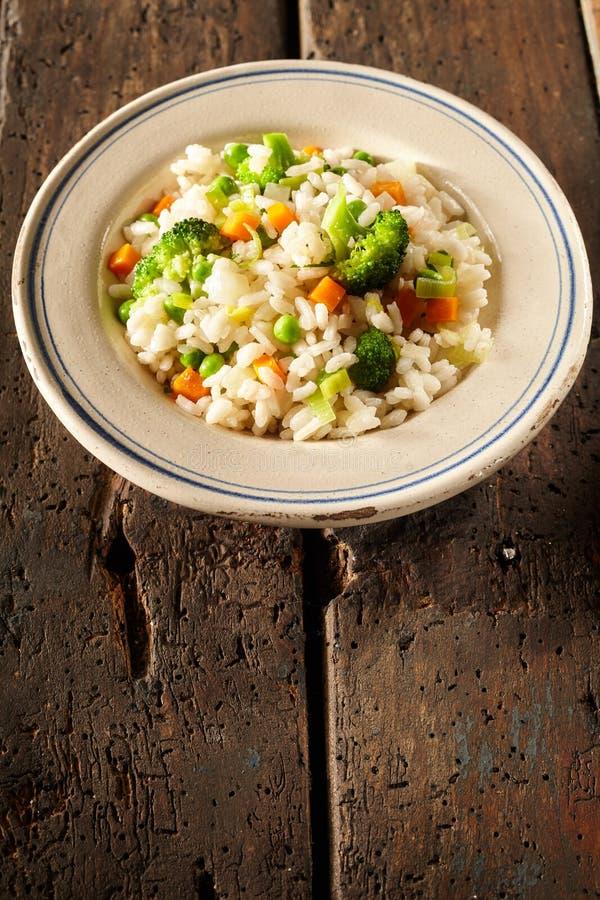 Schotel met risottorijst en kleurrijke groenten wordt gevuld die stock foto