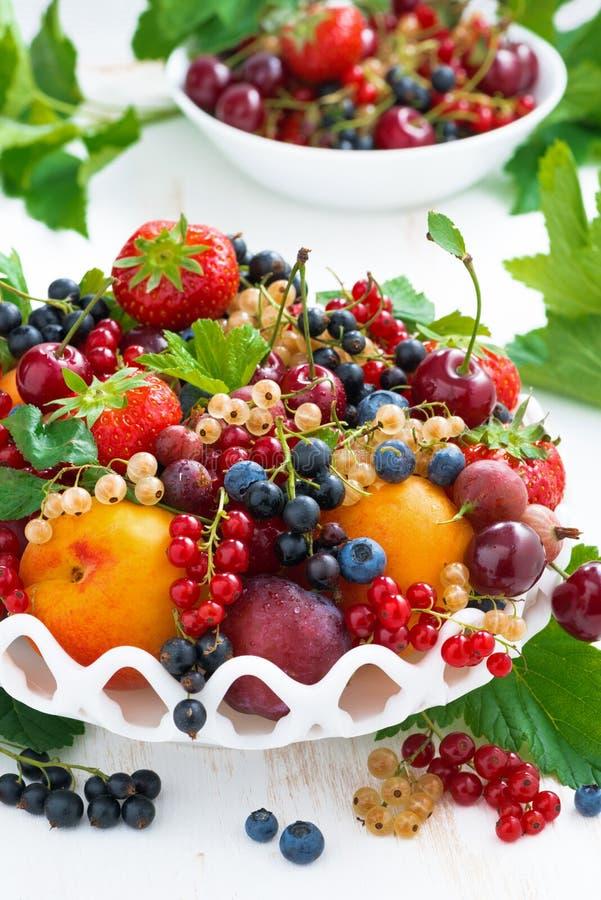 Schotel met vers seizoengebonden fruit en bessen op verticale lijst, royalty-vrije stock foto's